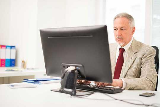 Foto 1 Commercialista al computer che sta analizzando la centrale rischi Banca d'Italia